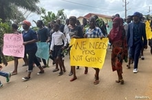 Schoolchildren, their parents and teachers hold a protest after gunmen opened fire at a school, killing at least six children as authorities claim, in Kumba, Cameroon, Oct. 25, 2020.
