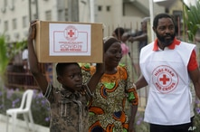 A child with his mother from Makoko Slum, carries their food parcel distributed by the Nigerian Red Cross, provided for those…
