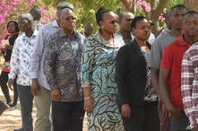 The ruling party CCM presidential candidate Dr. John Magufuli, third left, stands in line to cast his vote at Chamwino in Dodoma, Oct. 28, 2020.