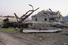 A destroyed building and vehicle after shelling by Azerbaijan's artillery during a military conflict outside Stepanakert, the separatist region of Nagorno-Karabakh, Oct. 19, 2020.