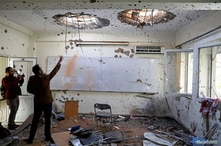 Afghan journalists film inside a classroom after an attack at the university of Kabul, Afghanistan, Nov. 3, 2020.