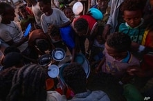 Tigray men who fled the conflict in Ethiopia's Tigray region, receive cooked rice from charity organization Muslim Aid, at Umm…