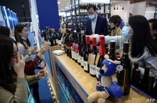 FILE - People taste wines from Australia at the Food and Agricultural Products exhibition at the third China International Import Expo (CIIE) in Shanghai, China, Nov. 5, 2020.