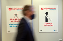A person walks past pictograms on December 1, 2020 in the vaccination centre at the football stadium in Duesseldorf, western…