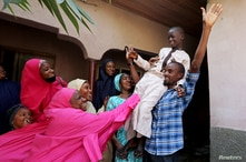 Muhammed Bello, a rescued student, is carried by his father as his relatives celebrate after he retuned home in Kankara,…
