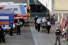 Paramedics escort a patient from the ambulance entrance to the emergency room at LAC + USC Medical Center during a surge of…