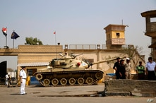 FILE - Egyptian security forces stand guard outside one of the entrances of Tora prison.