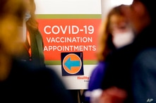 A COVID-19 vaccination appointments sign points the way at Edward Hospital in Naperville, Ill., Thursday, Dec. 17, 2020. Illinois…