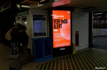 A digital sign shows that London is under coronavirus Tier 3 restrictions, the toughest level in England's three-tier system, at Euston railway station in London, Dec. 18, 2020.