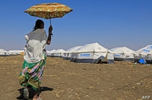 An Ethiopian refugee, who fled the Tigray conflict, walk in the Tenedba camp in Mafaza, eastern Sudan on January 8, 2021, after…
