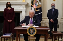 US President Joe Biden signs executive orders as part of the Covid-19 response as US Vice President Kamala Harris (L) and…