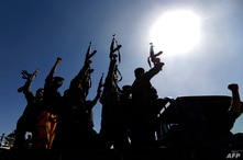 Newly recruited Houthi fighters chant slogans as they ride a military vehicle during a gathering in the capital Sanaa to…