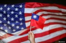 FILE PHOTO: An anti-government protester holds a Taiwan national flag as a U.S. flag flutters in the background during a…