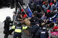 Pro-Trump protesters tear down a barricade as they clash with Capitol police during a rally to contest the certification of the…