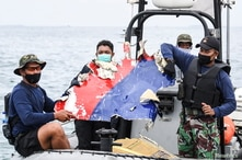 Indonesian Navy personnel carry debris believed to be from the Sriwijaya Air SJ-182 plane, which crashed into the sea, off the…