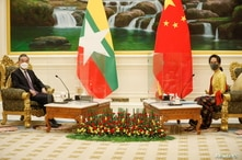 China's State Councillor and Foreign Minister Wang Yi is welcomed by and Myanmar's state counsellor Aung San Suu Kyi in Naypyitaw, Myanmar, Jan. 11, 2021.