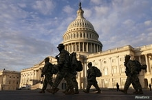 National Guard members walk in front of the U.S. Capitol after the House voted to impeach U.S. President Donald Trump.