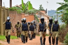Ugandan riot policemen patrol an area near the house of the presidential candidate and singer Robert Kyagulanyi Ssentamu, known…