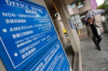 FILE - In this Dec. 30, 2011, photo,  a man walks past the US visa services entrance of the American Institute in Taiwan, the de facto American embassy, in Taipei, Taiwan.
