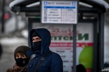 FILE - A man and a woman wearing face masks to protect against the coronavirus wait for a bus at a bus stop in central Moscow, Russia, Jan. 9, 2021.