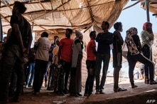 Eritrean refugees queue during a distribution of items organised the United Nations High Commissioner for Refugees (UNHCR) at…