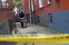 A NYC coroner carries an empty gurney at the scene of an alleged homicide in the Brooklyn borough of New York, U.S., Sept. 7, 2020.