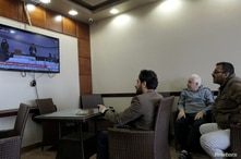 Men watch the elections to choose the new interim government on a TV screen at a cafe in Benghazi, Libya February 5, 2021…