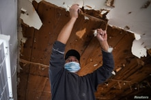 FILE PHOTO: A contractor removes material from a ceiling in a recently-purchased home that sustained water damage due to busted…
