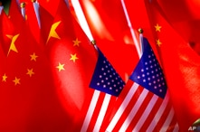 FILE - In this Sept. 16, 2018, file photo, American flags are displayed together with Chinese flags on top of a trishaw in…