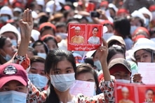 People holding images of detained civilian leader Aung San Suu Kyi and President Win Myint, call for their release during a rally against the military coup in Yangon, Myanmar, Feb. 7, 2021.