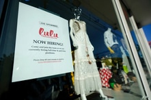 """FILE - A """"Now Hiring"""" sign is seen in a store window in the Wynwood Arts District of Miami, Florida, Jan. 27, 2021."""