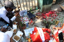 People mourn at the site where a young man died during a protest against the military coup, in Yangon, Myanmar, Feb. 28, 2021.