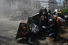 Protesters take shelter behind homemade shields after tear gas was fired during a demonstration against the military coup in…