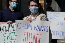 Protestors hold signs as they gather during a rally for Uyghur Freedom in New York on March 22, 2021. - The rally is for Uyghur…