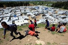 FILE - Syrian refugee children play together, as Lebanon extends a lockdown to combat the spread of the coronavirus disease (COVID-19) at a Syrian refugee camp in the Bekaa valley, Lebanon May 7, 2020.