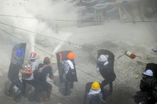 Tear gas and fire extinguisher gas float around protesters as they clash with riot police officers during a protest against the…