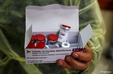 A health worker holds a box contains vials of AstraZeneca vaccine against the coronavirus disease (COVID-19) during a…