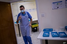 A health worker holds a Pfizer-BioNTech COVID-19 vaccine at the vaccination centre in Gibraltar, March 4, 2021.