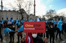 A protester from the Uyghur community living in Turkey, holds an anti-China placard during a protest in Istanbul, March 25, against the visit of China's FM Wang Yi to Turkey.