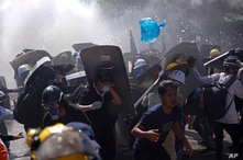 Protesters are dispersed as riot police fire tear gas during a demonstration in Yangon, Myanmar, March 8, 2021.