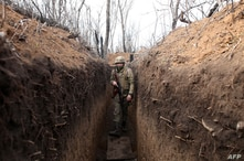 A Ukrainian serviceman walks in a trench on the frontline with Russia-backed separatists near town of Krasnogorivka, Donetsk…