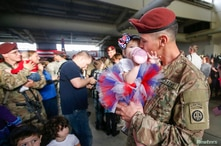 Sean Smith, a paratrooper with the 1st Brigade Combat Team, 82nd Airborne Division, kisses his daughter Olivia Rose Smith