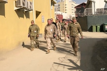 FILE - In this Jan. 31, 2020, file photo Marine Gen. Frank McKenzie, center, top U.S. commander for the Middle East, makes an…