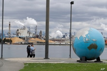 FILE - People walk past an Earth globe sculpture at Thea's Park in Tacoma, Washington, with the WestRock Paper Mill in the background, April 21, 2020.