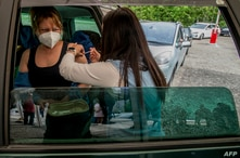 A woman receives a Pfizer/BioNTech vaccination against the novel coronavirus (Covid-19) in a car at a drive-in vaccination…