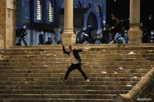 A Palestinian hurls stones at Israeli police during clashes at the compound that houses Al-Aqsa Mosque, known to Muslims as…