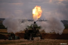 Israeli soldiers work at an artillery unit as it fires near the border between Israel and the Gaza strip.