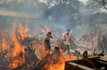 Relatives react to heat emitting from the multiple funeral pyres of COVID-19 victims at a crematorium in the outskirts of New…