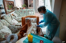 Nurse Pilar Rodríguez administers the COVID-19 vaccine to her patient Antonia Crespi Gomila, 93, at her home in the town of Sa…