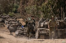 Israeli soldiers gather at a staging ground near the border with the Gaza Strip, in southern Israel, Sunday, May 16, 2021. (AP…